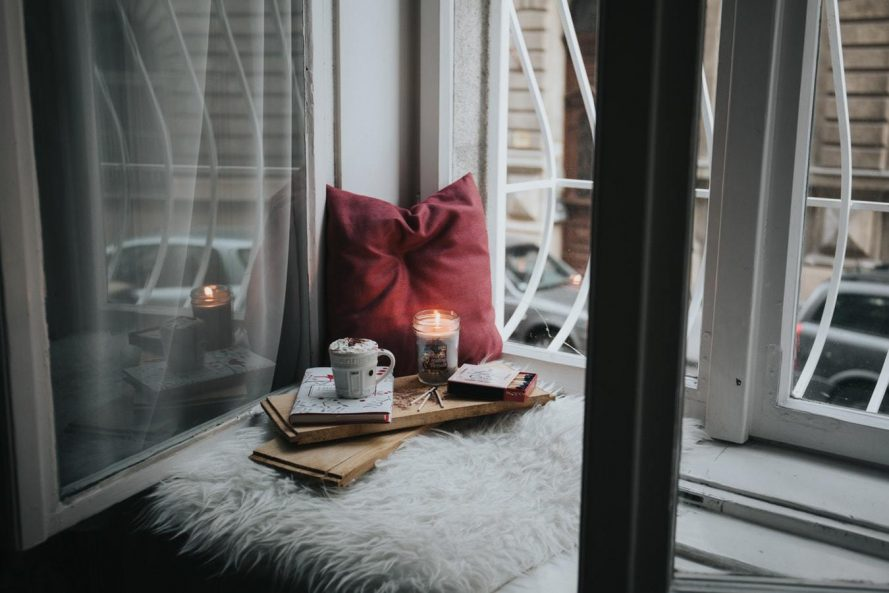 beside an open window is a maroon pillow and a tray with a candle, mug, and books