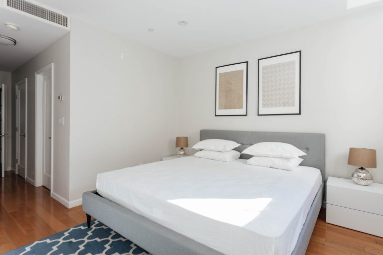 Calming bedroom with grey bed and two wall arts