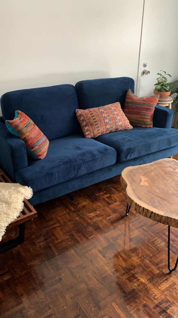 Midcentury modern living room with blue sofa and live edge coffee table