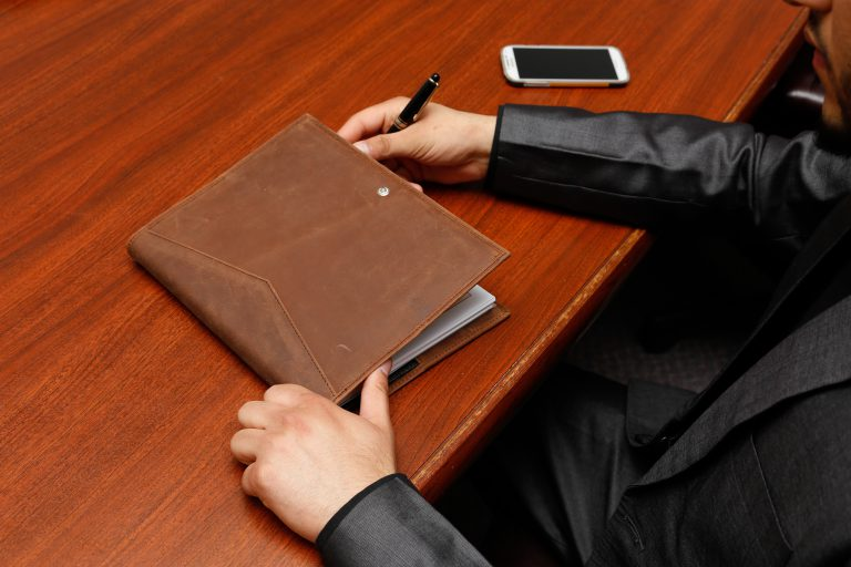 Close up of someone sitting at a wood table with a leather folio and smartphone.