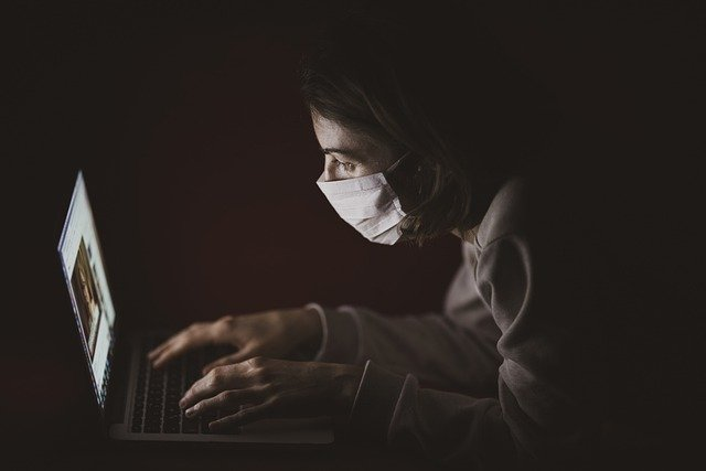 a person wearing a mask types on a laptop in a dark room