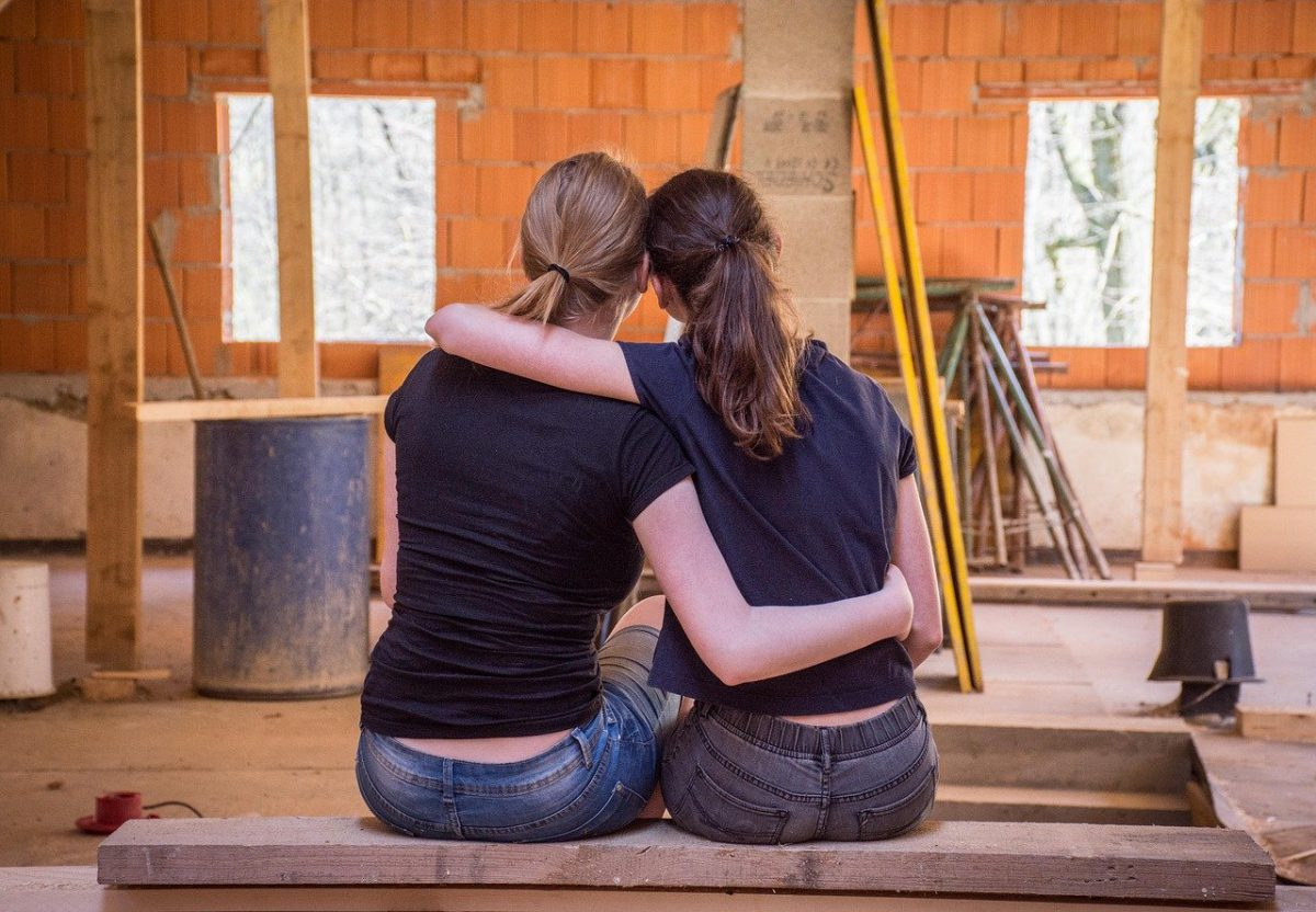 two women hugging in a house under renovation