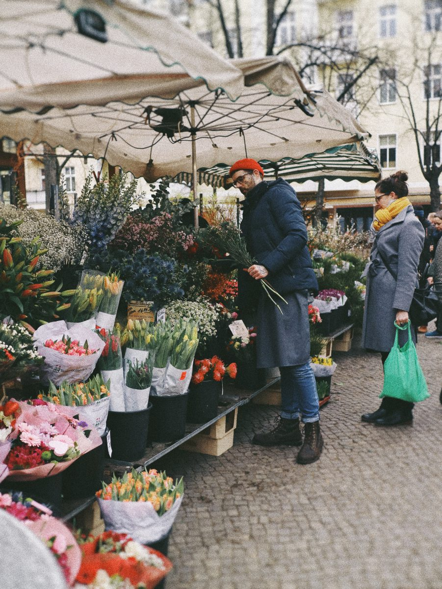 A man and woman at an outdoor flower market.