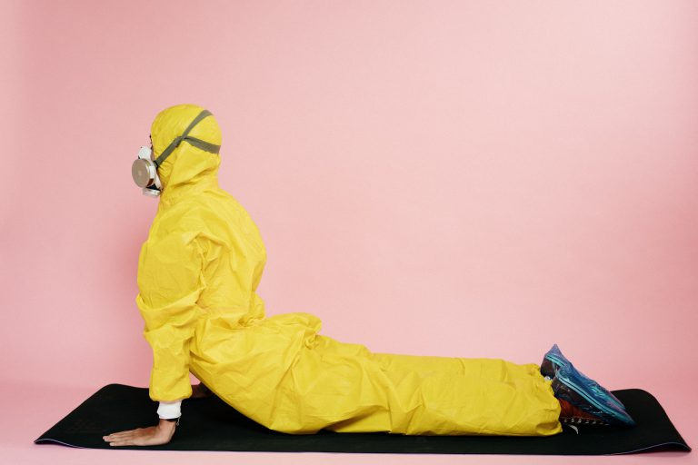 man in yellow protective suit stretching on yoga mat in quarantine