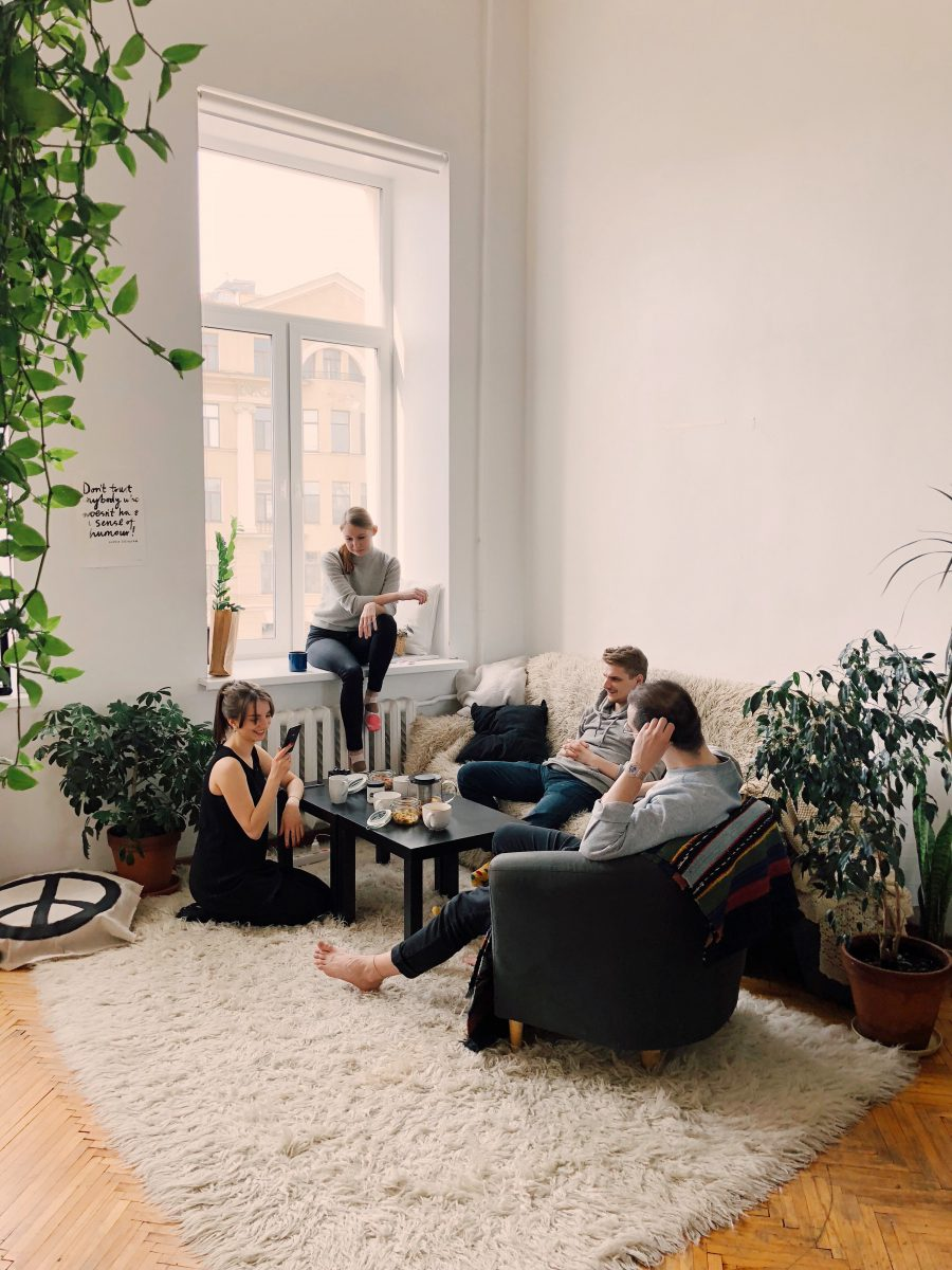 a group of people gather in a living room and chat