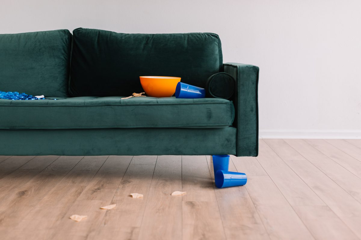 a dark teal couch with spilled chips on the ground and an overturned plastic cup