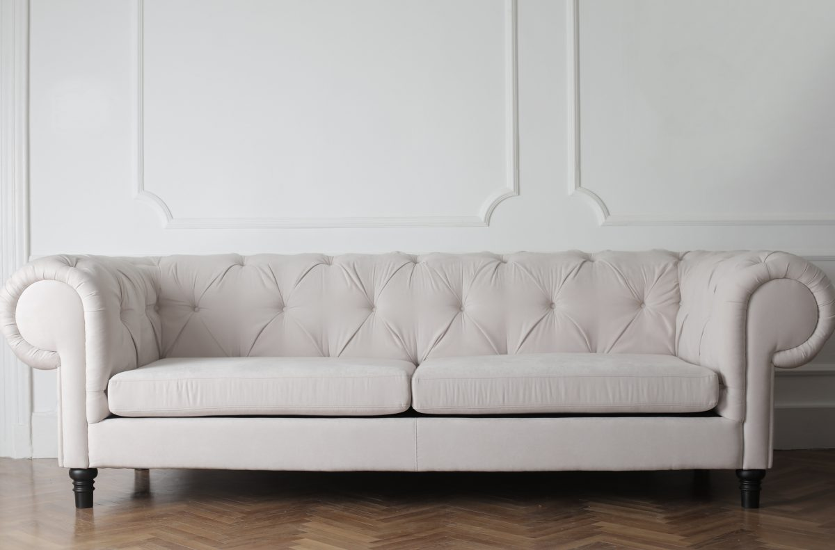 a white couch on wood floor and fancy white wall