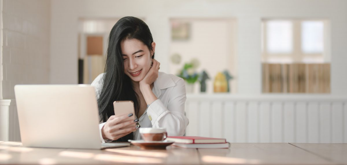 a woman looks down at her phone and smiles