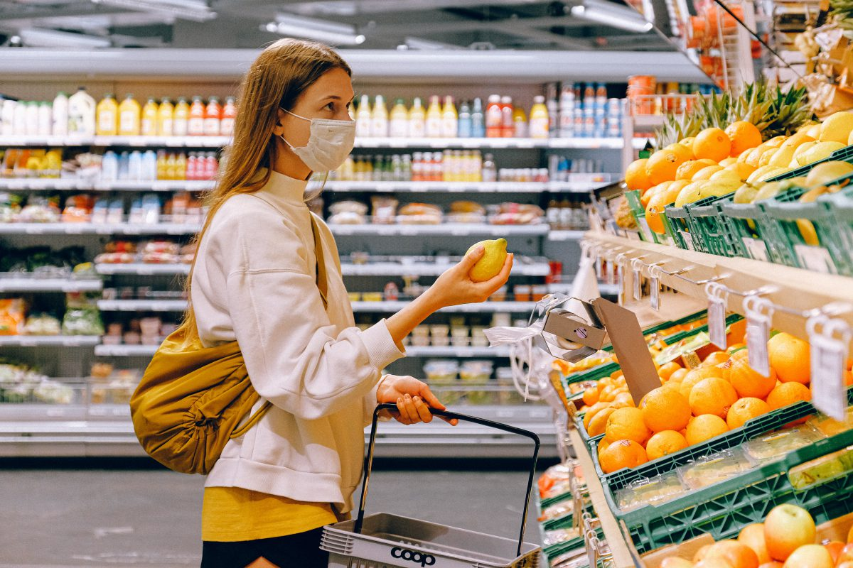 A woman is grocery shopping. She wears a yellow t-shirt and beige jacket and a face mask. She is holding a citrus fruit.
