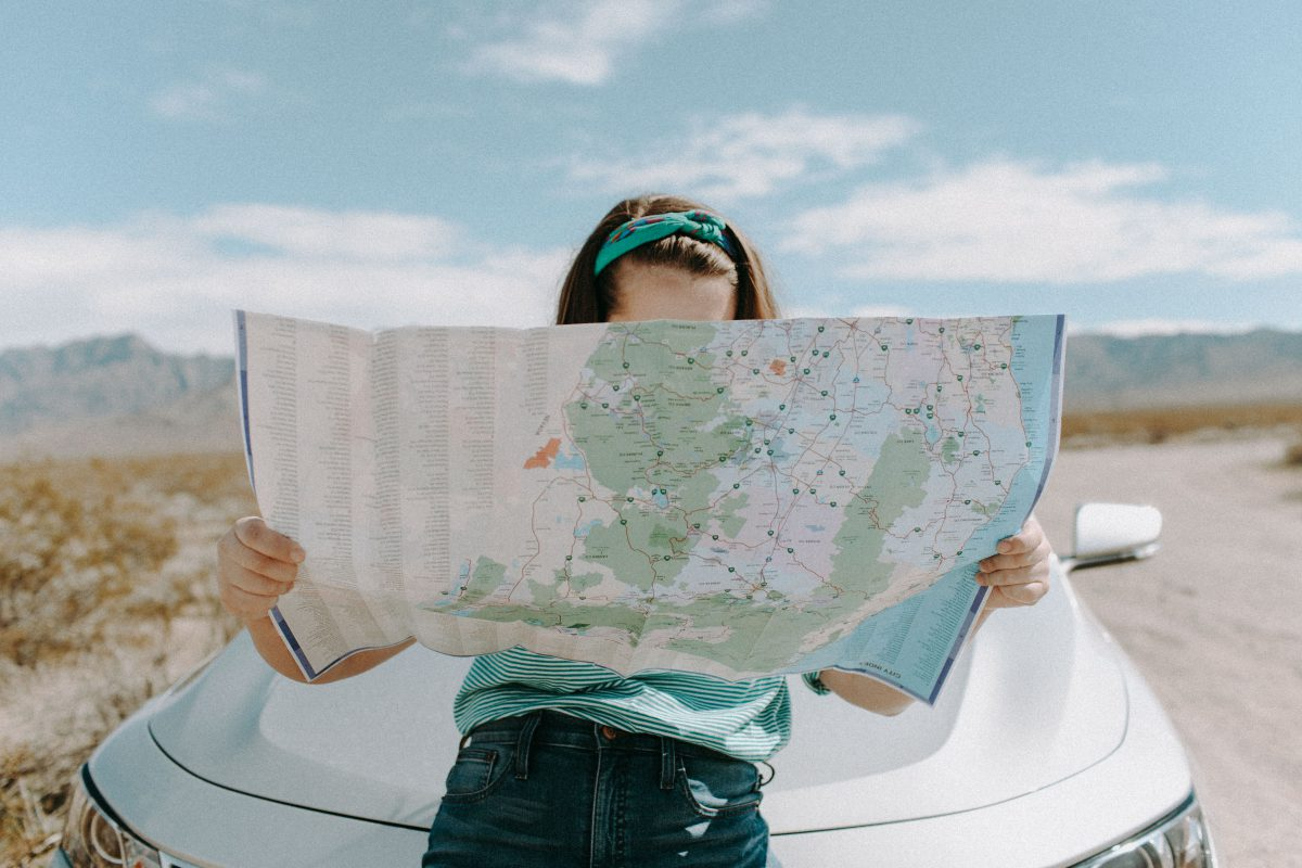 A woman looks down at a map and leans against the hood of a car.