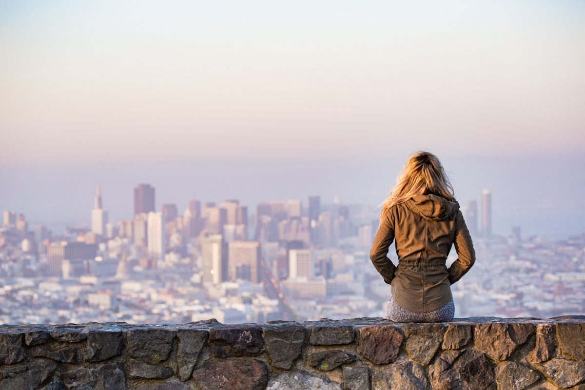 A woman on a rock platform views the city from far away. She faces away from the camera.