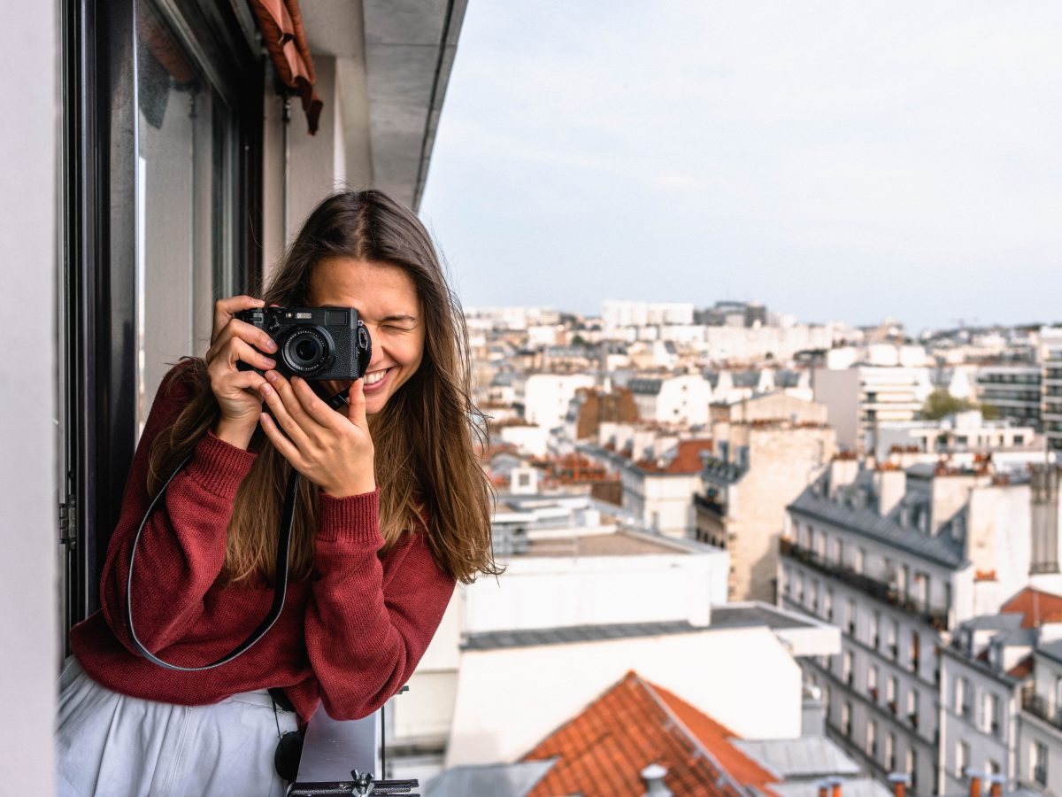 A woman wearing a maroon sweater on a balcony holds a camera. The city is visible behind her.